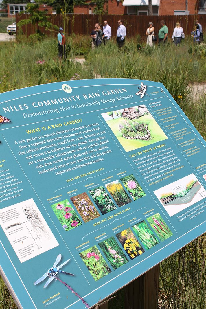 Rain Garden signage and a group touring the site.